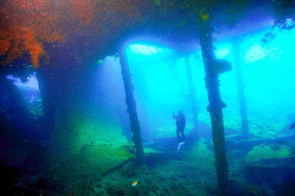 Tulamben dive & snorkel sites - scuba diver inside liberty shipwreck Tulamben